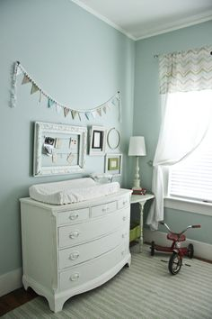 Love the color on the wall combined with the crisp white furniture and frame. I dig the pom pom swag, too.