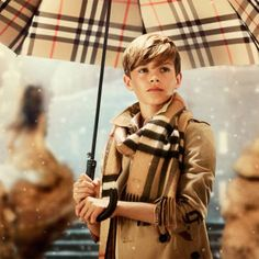 Romeo Beckham stars in the new Christmas advert from Burberry. Acting as the Santa of the city, Romeo runs around gifting glittery boxes to the crowds, all wearing Burberry macs - obviously. David E Victoria Beckham, Victoria And David, Burberry 2014, Burberry Prorsum, Burberry Outlet, Burberry Kids, David Beckham, Beckham Hair, Kids Fashion