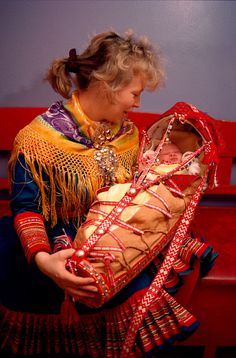 Sami mother with her baby in traditional cradle at christening. Kautokeino, Norway