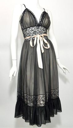 Lady Leonora 1950s black chiffon and pink nylon peignoir set. Nightgown of palest pink nylon has black chiffon overlay with lace trim cups, wide lace waist with pink satin ribbon sash. Robe has full sleeves gathered below elbow, lace collar and pink ribbon tie at throat. (gown)