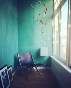 The conservatory. Green walls, leather chair, lotek lamp by Benno Premsela and a hanging mobile by Erica Geurkink.   Home, interior, inspiration, living room, green walls, brown, house, home, huis, interieur, Dutch, design, chair