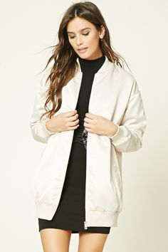 A satin bomber featuring a longline silhouette, zip-up front, ribbed trim, two front slit pockets, and long sleeves.
