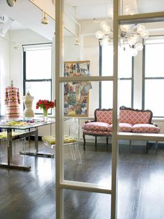 DESIGN STUDIO FOR CLOTHING/ACCESSORY LINE White space & dark floors.  Modernist glass top table; lucite chairs; Sputnik chandelier; Victorian settee; work space