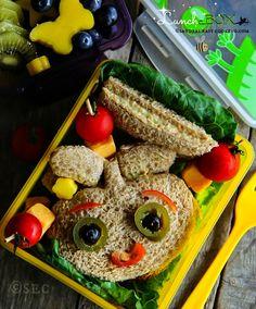 Delicious, homemade and easy bento -lunch box with chicken salad sandwiches, cheese, tomatoes and fresh fruits.