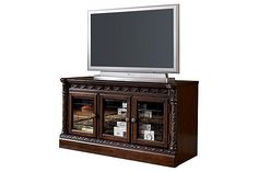 """The North Shore Narrow TV Stand from Ashley Furniture HomeStore (AFHS.com). A rich traditional design and exquisite details come together to create the ultimate in Old World style with the """"North Shore"""" entertainment wall."""