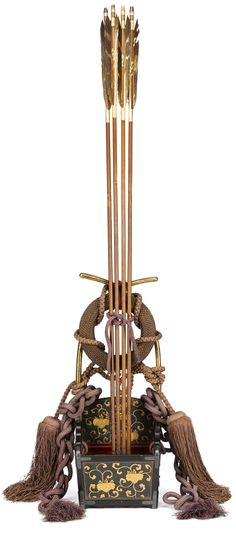 Ebira (quiver) with four arrows, 19th century, embossed leather decorated with paulownia vines in gold lacquer in a black-lacquered wood frame, the mounts in silver, the interior in red lacquer, the upright frame nashiji, fitted with tasseled silk cord and woven rattan tsurumaki (string holder), four fletched arrows with bamboo shafts and iron arrowheads 37 1/2in (95.3cm) high, including arrows.