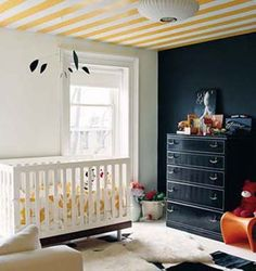Midnight navy wall in kids room and yellow striped ceiling