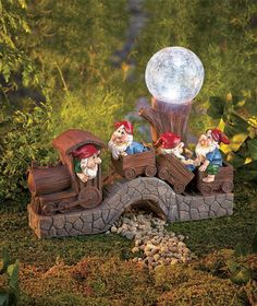 Give your garden or walkway a whimsical touch during the day and light at night with Solar Train with Gnomes. A happy party of gnomes is riding a train past a tree stump topped by a solar-lighted crackle glass globe. The solar panel on the back collects Garden Shop, Gnome Garden, Lawn And Garden, Gnome Statues, Garden Statues, Angel Statues, Solar Licht, Garden Globes, Gnome House