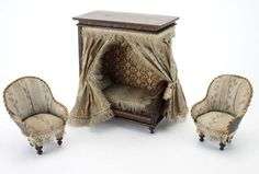 German dolls' house day bed with deep faux graining on side and top panels, lithographed paper walls with woven and printed cotton bedding, and curtains; two wood and card chairs upholstered in matching fabric.