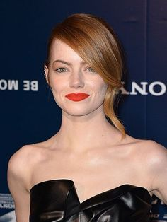 Emma Stone The Amazing Spider-Man 2 red carpet beauty look: a low updo with side-swept curled bangs and a fiery red lip with defined brows | allure.com