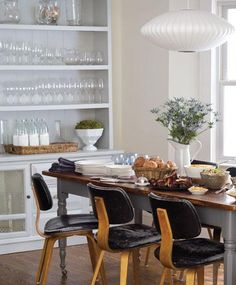 Virginia McDonald, Photographer  Farmhouse dining table with gray painted turned legs and black Gus Modern Thompson chairs and George Nelson saucer pendant chandelier.