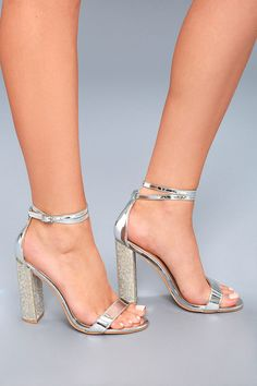 Complete your LBD with the Viv Silver Rhinestone Ankle Strap Heels! Metallic vegan leather forms a peep-toe upper, and looping adjustable strap with silver buckle. Stunning clear rhinestones adorn the block heel for a glam touch.