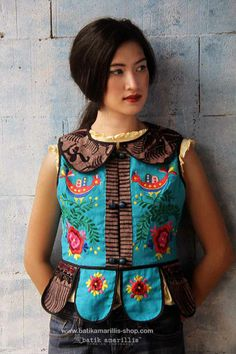 batik amarillis's piccola vest  Piccola jacket in beautiful Teal- Blue Linen   vest with  multi colored Hungarian folk embroidery meets tenun batik  gedog Tuban,Indonesia Take a fresh, sweet & whimsical approach to power dressing with this Krakow-Poland classic traditional folklore inspired jacket.  The beauty essential is reworked with a contrast-coloured batiks,unique cuttings ,trims,glossy beaded buttons,it has fitted waist with unique peplum petals