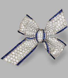 DIAMOND AND SAPPHIRE BOW BROOCH Set with round diamonds weighing approximately 5.00 carats, accented by calibré-cut sapphires weighing approximately 2.25 carats, mounted in platinum.