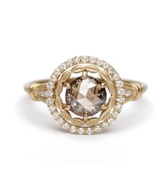 Channel your inner Greek Goddess with this unique and utterly captivating engagement ring. Crafted in solid 18kt matte yellow gold, a central 0.85ct champagne, mogul-cut diamond is framed by a sculpted leafy halo and a second surround of tiny twinkling diamonds(0.20ctw). This one-of-a kind ring features both a low profile and larger finger coverage without losing the ability to stack it with your favorite eternity bands. Luminous and ethereal, this delicate beauty is in a class of its…