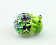 Lampwork frog bead. The floral lampwork bead has cobalt blue base and light blue flower. The flowers are encased inside clear glass. .      Size: