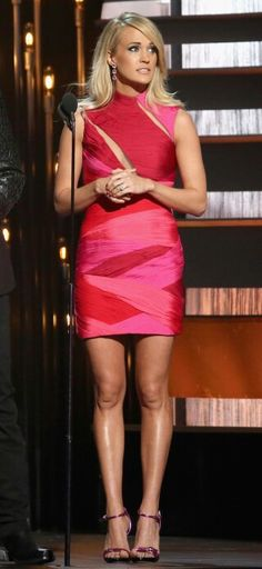 Carrie Underwood leggy at CMAs in a red body con dress and high heels