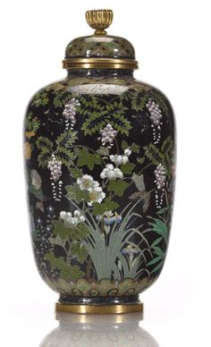 A small cloisonne enamel vase and cover By the workshop of Namikawa Yasuyuki (1845-1927) The cylindrical vase tapering slightly toward the bottom and set on a splayed foot, the domed cover surmounted with a gilt-metal chrysanthemum finial decorated in polychrome enamels and silver wires with stands of flowers, maples, birds and butterflies, the shoulder and foot designed with stylized floral bands, signed on a silver tablet Kyoto Namikawa