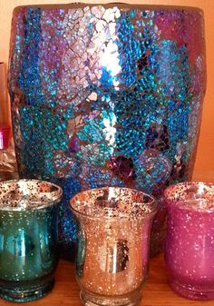 The big vase is actually a trash bin for the bathroom, paid about $25 at HomeSense. The three little cups are candle holders (votive, scented, etc), $1.50 each at Dollarama. When the sun hits these, wow!