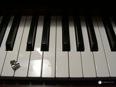 Another angle of piano charm on keyboard