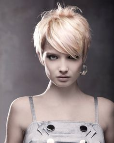 Lovely execution of this asymmetrical pixie cut and earing! Short backs and sides with long diagonal bangs are everywhere right now and it looks so modern.