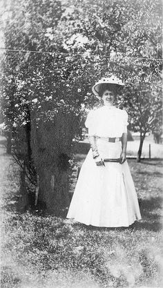 Portrait of Bess Wallace, wearing a long light-Colored gown and picture hat, carrying a parasol. She is posing next to a rosebush in the yard of her home at 219 North Delaware Street, Independence, Missouri.