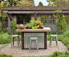 Islands aren't just for the kitchen; they work wonders in outdoor rooms too! A wood-and-metal island and barstools are a budget-savvy choice for outdoor dining. A tabletop salad garden adds a soft touch while a pea gravel patio promises easy upkeep underfoot./ #outdoorwood