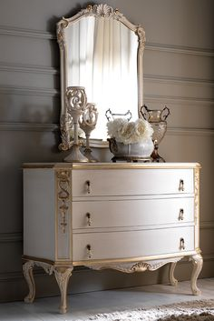 Shown here in an antiqued ivory finish together with hand painted antiqued gold to the carved detailing of both the chest of drawers and the beautiful mirror which completes the set. Embellished with unique delicate handle fittings with tear drop ceramic pulls. The Ornate Italian Rococo Chest of Drawers and Mirror Set is the most striking addition to any setting. Above all, truly versatile.