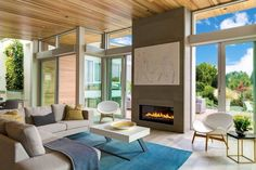 Delbrook Residence by Garret Cord Werner Architects I love the chunkiness, and strong lines, of the white beams atop the sliding glass doors and tall windows. The wood ceiling warms up the room. The blue rug is a great accent for all the brown tones (and white). And my, what a view… in tony North Vancouver, BC.