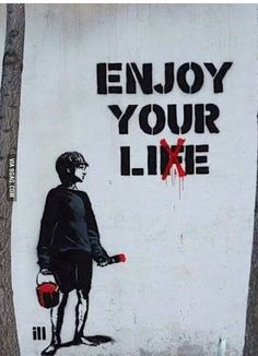 "In this image, we see a young man holding a paint brush and bucket filled with red paint, correcting graffiti on a wall which reads ""Enjoy your life."" The boy has taken a paintbrush and crossed out the letter ""F"" so it now reads: ""Enjoy your lie."""