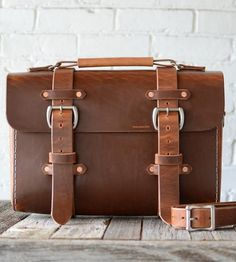Tote all your essentials (laptop included) in style with this sturdy leather satchel. It's drum-stuffed with heavy tallow, which makes it exceptionally durable, and outfitted with nickel hardware, which makes it exceptionally handsome. Think it looks awesome now? Just give it a few years — this leather bag only gets better with time.