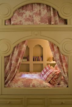 This triple-level bed was built to look like a fairy castle or doll's house. As well as the main bed, there are mattresses in the drawer below and the niche above the central opening to accomodate friends for a pajama party.