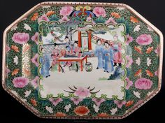 Description: An octagonal Chinese famille rose platter with raised edges, decorated in the typical famille rose palette, with a central 'C' scroll medallion, containing a figural pavilion scene, depicting female figures around a table, one of them playing the Chinese zither Guzheng, accompanied by standing dignitaries, dressed in long flowing robes.  Date: late 20th  www.collectorstrade.de
