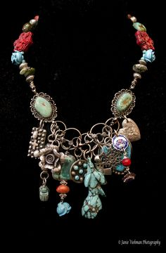 Turquoise Rose Treasure Necklace!  This piece has incredible antique flower beads with a plethora of turquoise and silver pendants hanging from handcrafted chain. The centerpiece is a beautiful antique piece of turquoise carved into the shape of a rose.