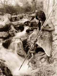 """Here for your enjoyment is an exciting photograph called """"Watching For Salmon"""". It was made in 1923 by Edward S. Curtis. The photo illustrates a Hupa Fisherman with a spear, standing on the bank, gazing into a stream."""