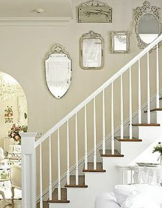 White and wood staircase with beige walls and antique mirrors.