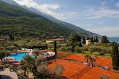 Club Hotel Olivi - Tennis Center Malcesine The hotel lies on the shores of Lake Garda at the foot of Monte Baldo, enclosed in a 30,000 m² park, with 9 tennis courts and a large heated pool.