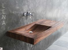 Lena's design is pure and minimalist in all its lines, soft curves and angles. The basin is smoothly  integrated into the surface. Running water onto the wood will be a daily reminder of the  serenity of a natural stream. The piece comes in golden reclaimed teakwood, or the darker,   warmer American walnut.