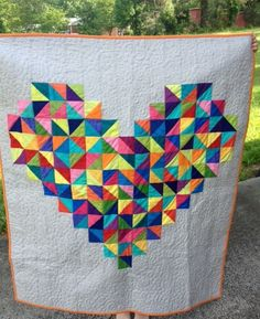 half square triangles! <3 Red Poppy Quilts (source no longer availiable). Heart quilt with a big center heart made of colourful scrap triangles.