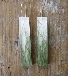 Grass Dangle Earrings by Fernworks on Scoutmob Shoppe  These outdoorsy dangle earrings feature real blades of grass encased in resin against an off-white wooden background.