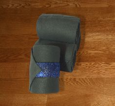 """Equine Polo Wraps/Gray Polo Wraps w/Blue Galaxy Velcro Strap. Made with quality gray fleece and industrial strength velcro to ensure a proper hold. Two sizes offered: Pony: 2 yards (6ft) length, 4"""" wide Horse: 9 ft front, 11 ft hind length, 5"""" wide."""