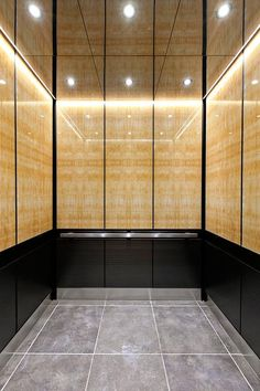LEVELe-105 Elevator Interior with upper panels in ViviStone Honey Onyx, Standard finish; lower panels in Fused Graphite, Sandstone finish, Dallas pattern; Handrail panel in Fused Graphite, Seastone finish; Quadrant Handrail in Satin Stainless Steel; Elevator Ceiling in Fused Nickel Silver, Mirror finish at 176 Broadway, New York, New York