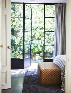 The doors and the outdoors are on the same level.  bedroom, outdoors, woven bench, zig zag flame stitch bedding, photo by Paul Barbera