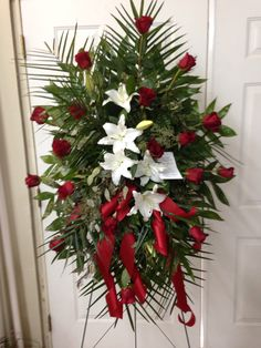 Fresh funeral spray using red roses, white lilies, seeded eucalyptus with red ribbon.