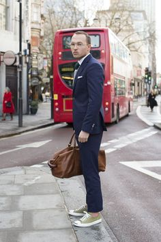 Wearing Archibald Optics glasses with a Riess suit, shirt, tie and jumper, Uniqlo socks, Converse Jack Purcells and carrying a Mulberry bag.