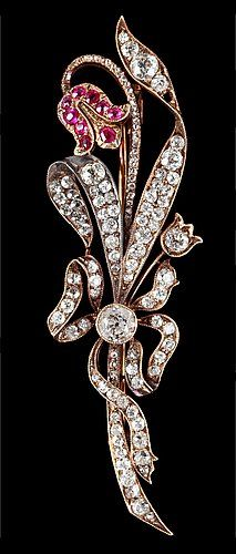 A DIAMOND AND RUBY BROOCH, 1890'S. Gold/silver.