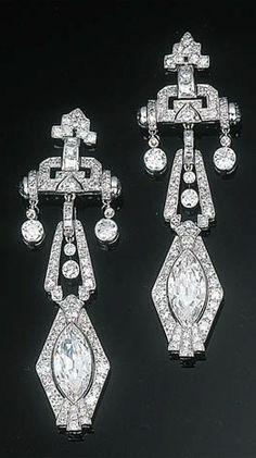 A Pair of Art Deco Diamond Ear Pendants Each comprising a marquise-cut diamond within a circular-cut diamond frame suspended from a diamond-set geometric surmount and diamond collet, circa 1930