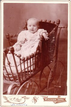 .Baby Isabella sits up and peers out of her ornate baby carriage. She has a terrific smile. The photographer is Robert I Steele (1861-1945)