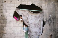 A Palestinian boy looks out of his damaged house after a ceasefire was declared, in the east of Khan Younis in the southern Gaza Strip August 27, 2014. REUTERS/Ibraheem Abu Mustafa