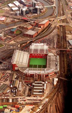 Old Trafford towers over the local terraced streets following the Champions League victory against Bordeaux as work continues to take place on expanding the West stand in March 2000